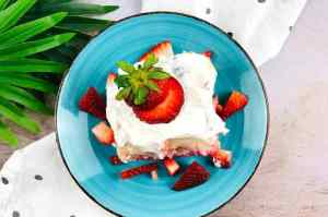 slice of strawberry poke cake on a blue plate