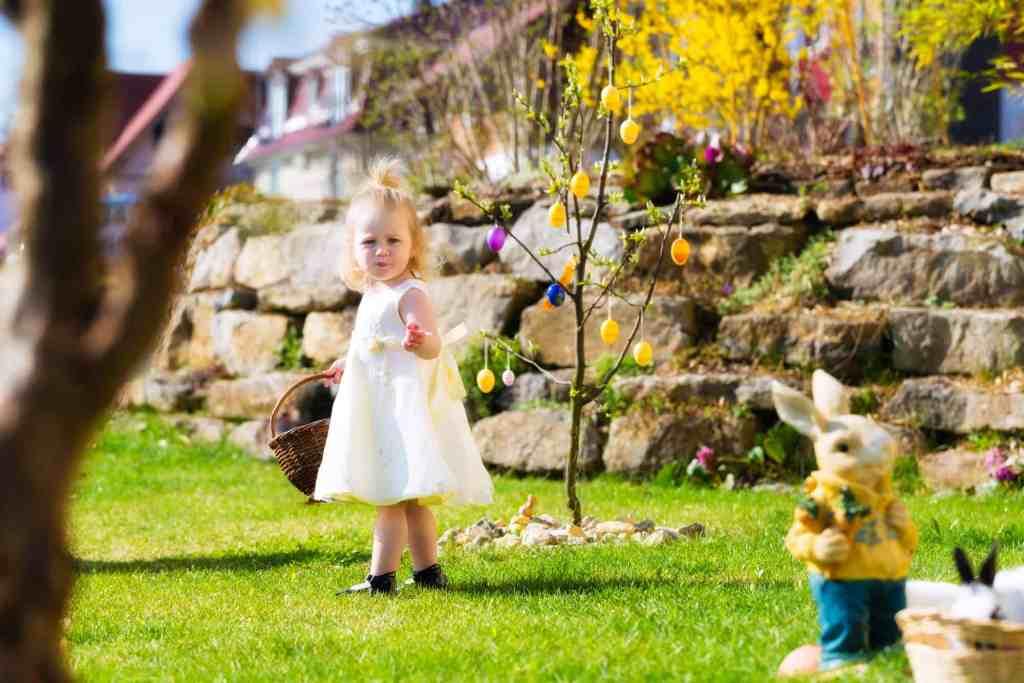 Little Girl on an Easter Egg scavenger hunt on a meadow in spring, she holding a basket or Easter basket