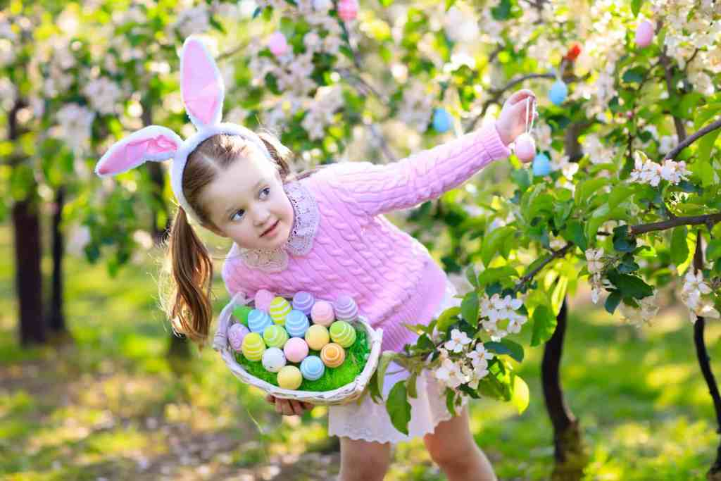 Child on Easter egg hunt in blooming cherry tree garden