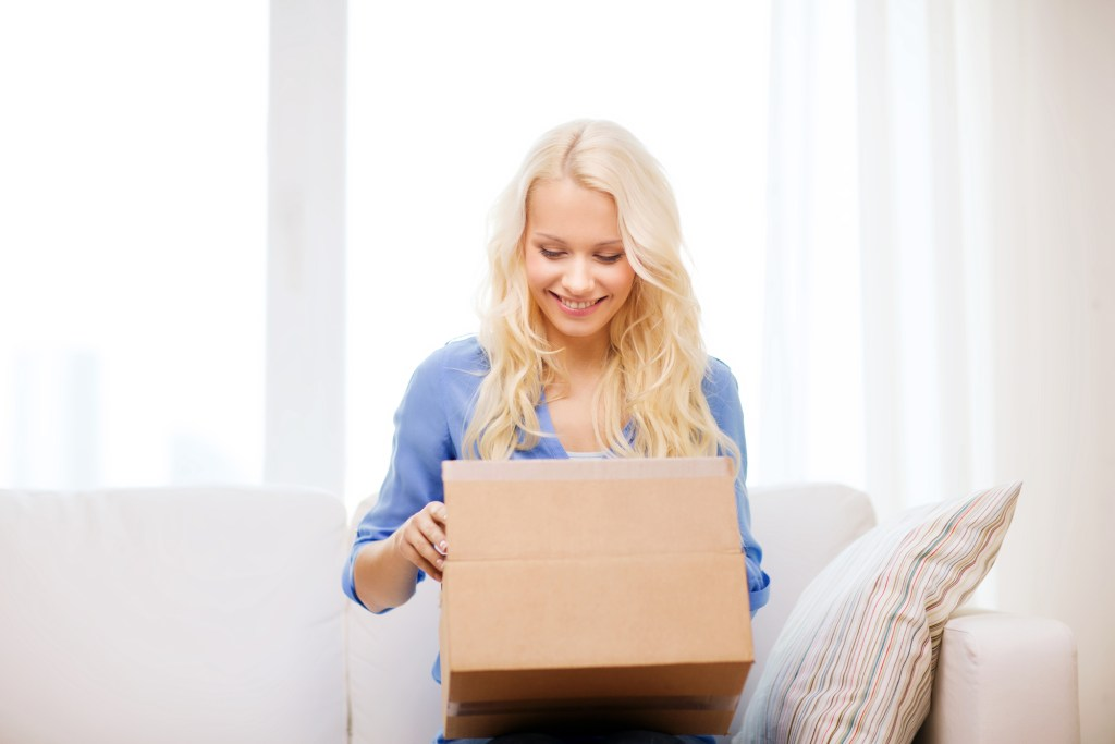 smiling woman opening a subscription box