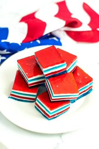 stacked red white and blue jello jigglers on a plate