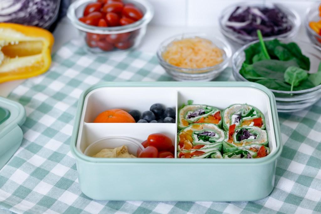 Bento box with pinwheels, tomatoes, and fruit