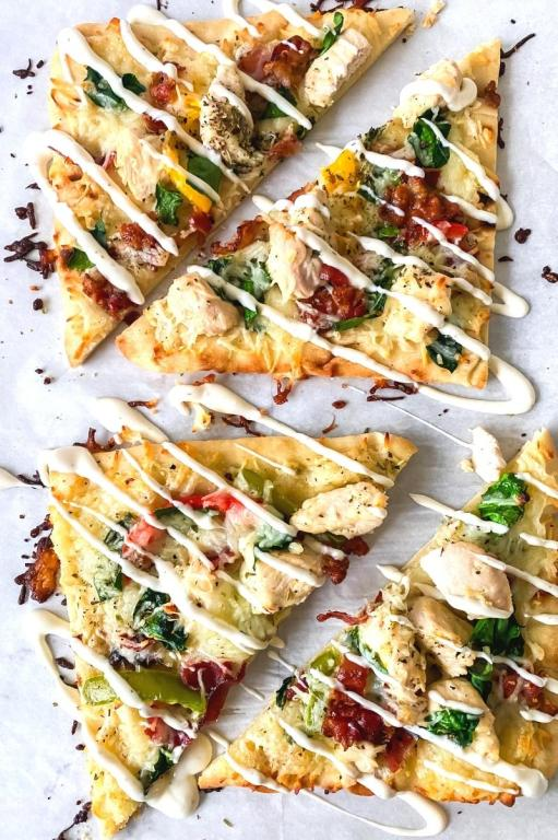 baked chicken bacon ranch flatbread with ranch drizzled on top