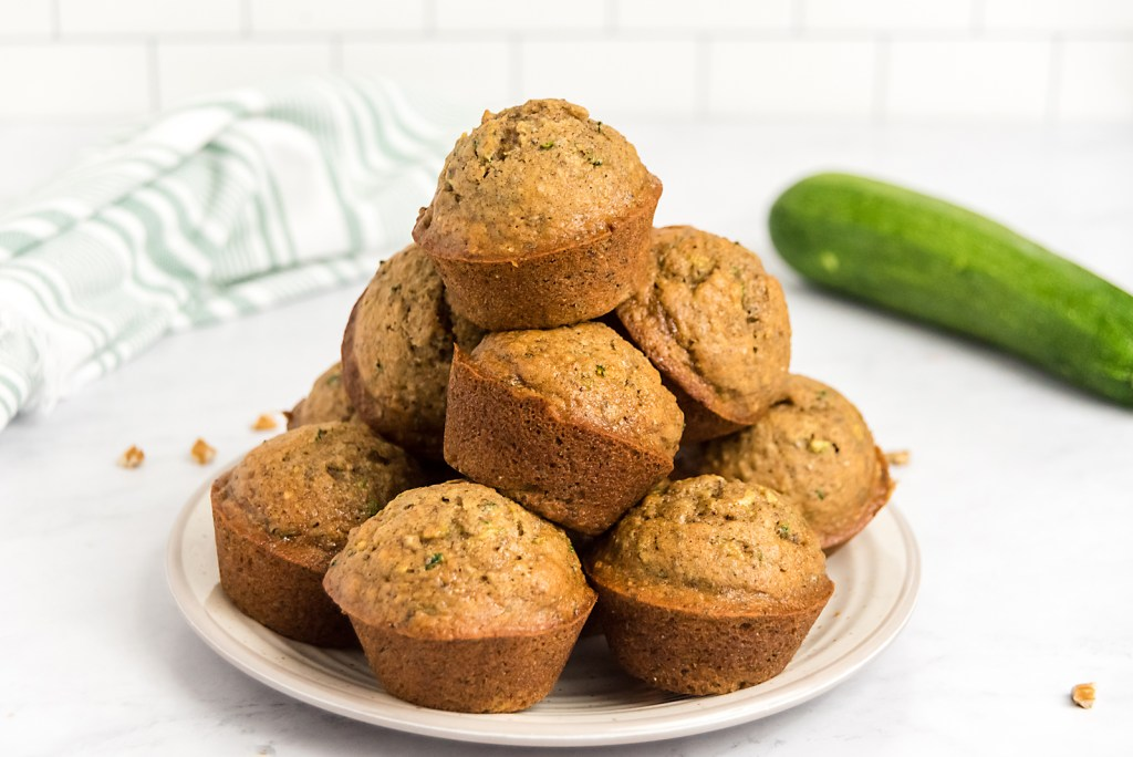 baked zucchini muffins stacked on a plate