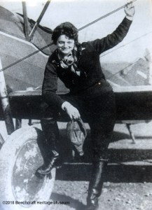Black and white photo of Louise Thaden next to her airplane