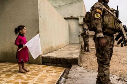 """2 novembre 2016, Gogjali, Mossoul-Est. Pendant que les hommes du premier bataillon de l'ISOF 1 du colonel Mohaned sécurisent les ruelles du quartier, une petite fille sort de chez elle à la rencontre des soldats, un drapeau blanc à la main. © Alvaro Canovas / Paris Match November 2, 2016, Gogjali, eastern Mosul. While men from the first battalion of the Iraqi Special Operations Forces (ISOF-1) led by Colonel Mohaned were securing the streets, a little girl emerged from her house carrying a white flag. © Alvaro Canovas / Paris Match Photo libre de droit uniquement dans le cadre de la promotion de la 29e édition du Festival International du Photojournalisme """"Visa pour l'Image - Perpignan"""" 2017 au format 1/4 de page maximum. Résolution maximale pour publication multimédia : 72 dpi Mention du copyright obligatoire. The photos provided here are copyright but may be used royalty-free for press presentation and promotion of the 29th International Festival of Photojournalism Visa pour l'Image - Perpignan 2017. Maximum size printed: quarter pageMaximum resolution for online publication: 72 dpi Copyright and photo credits (listed with captions) must be printed."""
