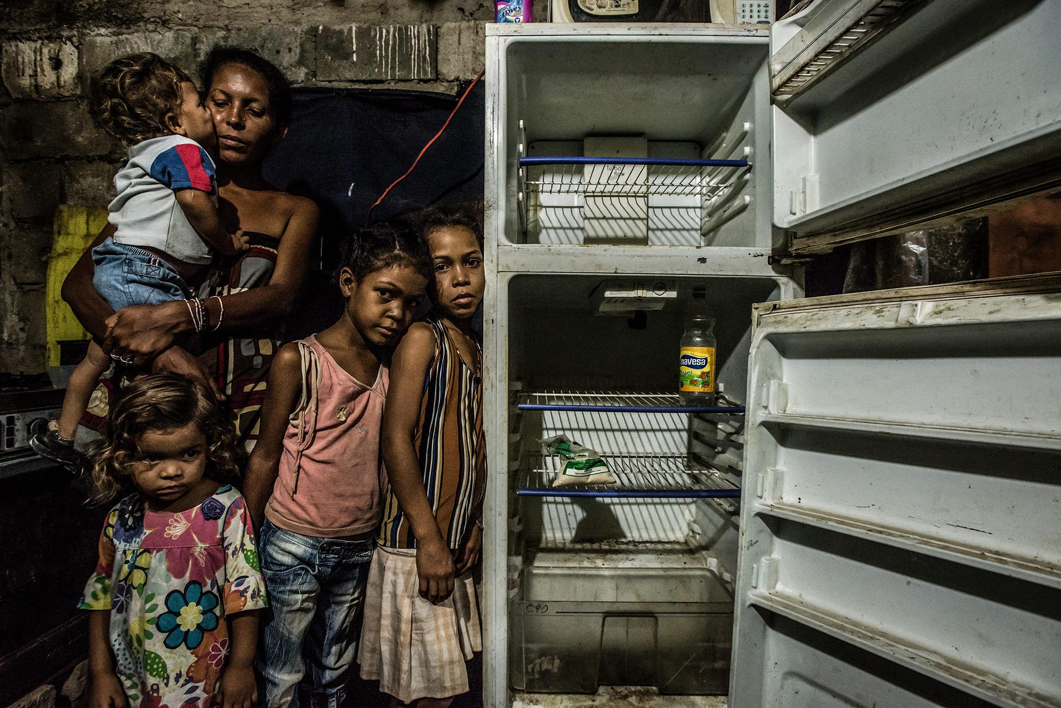 """Leidy Cordova (37 ans) avec quatre de ses cinq enfants : Abran (1 an), Deliannys (3 ans), Eliannys (6 ans) et Milianny (8 ans). La famille n'a pas mangé depuis le déjeuner de la veille, à savoir une « soupe » qui n'était autre qu'un bouillon de peau de poulet. Le réfrigérateur ne fonctionne pas et contient les seules denrées du foyer : un paquet de farine de maïs à moitié vide et une bouteille de vinaigre. 16 juin 2016. © Meridith Kohut pour The New York Times Leidy Cordova (37) with four of her five children: Abran (1), Deliannys (3), Eliannys (6), and Milianny (8). The family had not eaten since lunch the day before, and that was """"soup"""" made by boiling chicken skin and fat. The refrigerator is not working, and contains the only food in the house: half a bag of flour and a bottle of vinegar. June 16, 2016. © Meridith Kohut for The New York Times"""