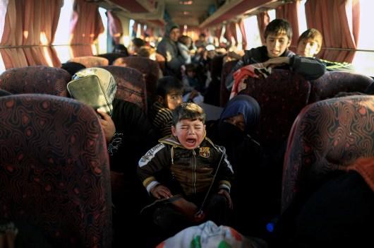 """Après avoir fui leur village pris par Daech, un garçon et sa famille dans un car qui les emmène au camp de déplacés de Hammam al-Alil, au sud de Mossoul. Irak, 22 février 2017. After fleeing a village controlled by Islamic State fighters, a boy and his family are in a bus that will take them to the refugee camp in Hammam al-Alil, south of Mosul, Iraq. February 22, 2017. © Zohra Bensemra / Reuters Photo libre de droit uniquement dans le cadre de la promotion de la 29e édition du Festival International du Photojournalisme """"Visa pour l'Image - Perpignan"""" 2017 au format 1/4 de page maximum. Résolution maximale pour publication multimédia : 72 dpi Mention du copyright obligatoire. The photos provided here are copyright but may be used royalty-free for press presentation and promotion of the 29th International Festival of Photojournalism Visa pour l'Image - Perpignan 2017. Maximum size printed: quarter pageMaximum resolution for online publication: 72 dpi Copyright and photo credits (listed with captions) must be printed."""