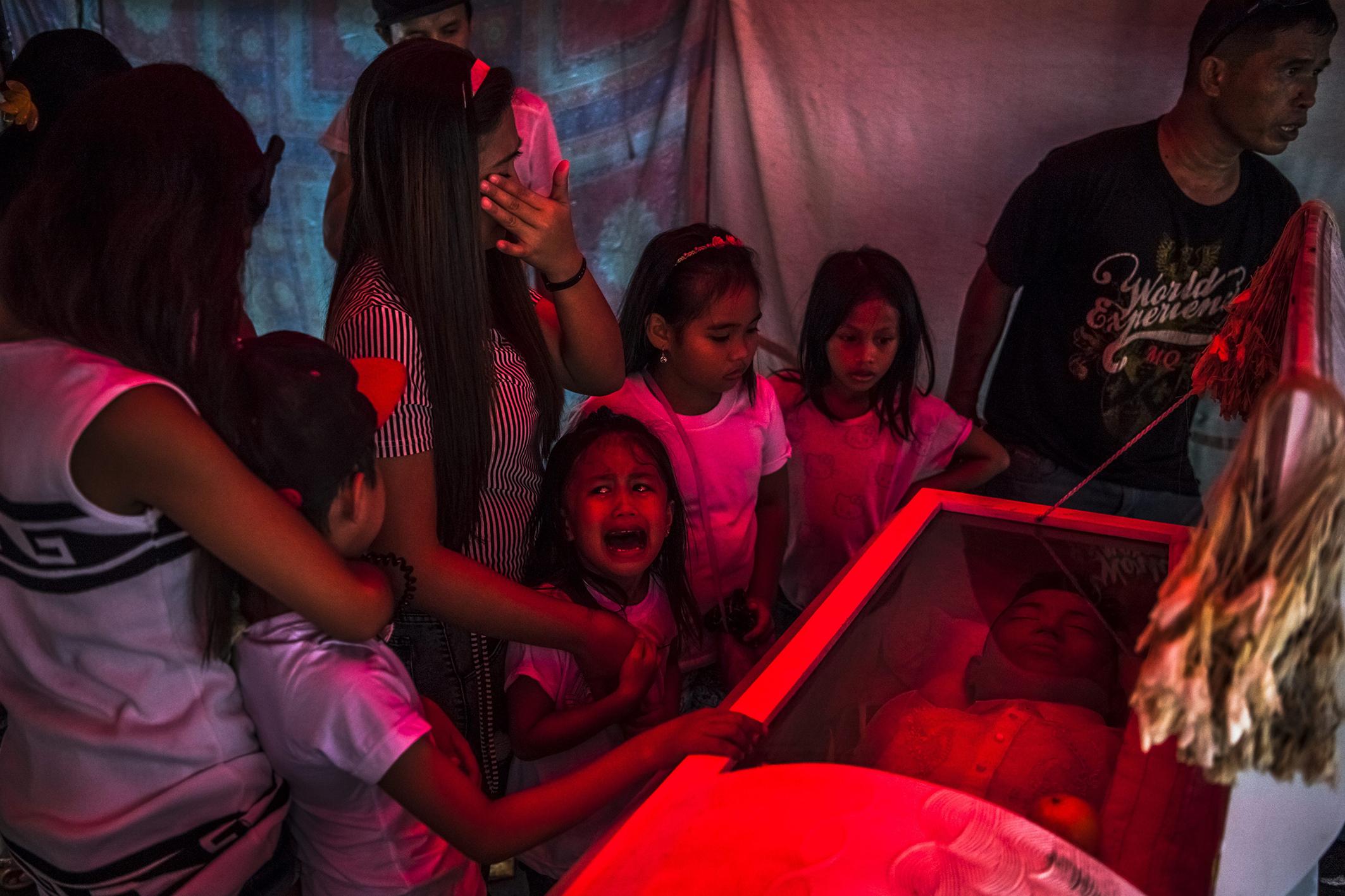 """La souffrance de la petite Jimji (6 ans) qui hurle « Papa ! » avant les obsèques de Jimboy Bolasa (25 ans). Des traces de torture et de blessures par balles étaient visibles sur le corps, retrouvé sous un pont. Selon la police, c'était un dealer ; selon ses proches, il avait répondu à l'appel du président Duterte et voulait suivre une cure de désintoxication. Manille, 10 octobre 2016. © Daniel Berehulak pour The New York Times Jimji (6), in anguish screaming """"Papa!"""" before the funeral of Jimboy Bolasa (25). His body, showing signs of torture as well as gunshot wounds, was found under a bridge. The police said he was a drug dealer, but according to his family, Bolasa had surrendered earlier, answering President Duterte's call to follow what was supposed to be a drug-treatment program. Manila, October 10, 2016. © Daniel Berehulak for The New York Times Photo libre de droit uniquement dans le cadre de la promotion de la 29e édition du Festival International du Photojournalisme """"Visa pour l'Image - Perpignan"""" 2017 au format 1/4 de page maximum. Résolution maximale pour publication multimédia : 72 dpi Mention du copyright obligatoire. The photos provided here are copyright but may be used royalty-free for press presentation and promotion of the 29th International Festival of Photojournalism Visa pour l'Image - Perpignan 2017. Maximum size printed: quarter pageMaximum resolution for online publication: 72 dpi Copyright and photo credits (listed with captions) must be printed."""