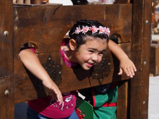 Une petite fille se prête avec humour aux supplices du Moyen Age