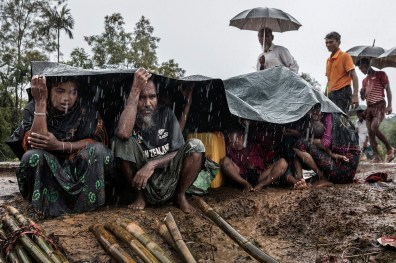 "Kutupalong, Bangladesh, 17 septembre 2017. Sous la pluie torrentielle de la mousson, une famille nouvellement arrivée attend un abri. Kutupalong, Bangladesh, September 17, 2017.  A newly arrived family, caught in the torrential monsoon rain, is waiting for shelter. © Paula Bronstein / Getty Images Photo libre de droit uniquement dans le cadre de la promotion de la 30e édition du Festival International du Photojournalisme ""Visa pour l'Image - Perpignan"" 2018 au format 1/4 de page maximum. 