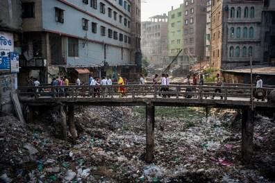"Dans le quartier de Keraniganj qui abrite de nombreux ateliers de confection, le lit d'un canal qui se jetait dans la rivière Buriganga est rempli de détritus. L'eau n'atteint plus la rivière en raison de la masse de déchets accumulés tout au long du canal. In Keraniganj, a district with many garment factories, the canal once flowed into the Buriganga River, but is now choked with waste stopping the water from reaching the river. © Gaël Turine / MAPS Photo libre de droit uniquement dans le cadre de la promotion de la 30e édition du Festival International du Photojournalisme ""Visa pour l'Image - Perpignan"" 2018 au format 1/4 de page maximum. 