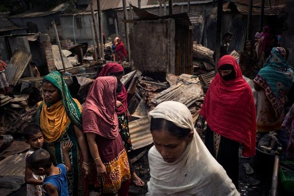 """Dans le quartier d'Abdullahpur, en bordure de la rivière Tongi Khal, 22 familles ont perdu leurs cases dans un incendie. Toutes les femmes travaillent dans l'industrie polluante du textile. La saturation démographique dans Dhaka oblige de nombreuses familles à vivre dans la précarité et la promiscuité. In the neighborhood of Abdullahpur on the Tongi Khal River, the huts of 22 families were destroyed by fire. Local women work in the textile industry which causes high levels of pollution. With the population of Dhaka, families live in difficult, overcrowded conditions. © Gaël Turine / MAPS Photo libre de droit uniquement dans le cadre de la promotion de la 30e édition du Festival International du Photojournalisme """"Visa pour l'Image - Perpignan"""" 2018 au format 1/4 de page maximum. Résolution maximale pour publication multimédia : 72 dpi Mention du copyright obligatoire. The photos provided here are copyright but may be used royalty-free for press presentation and promotion of the 30th International Festival of Photojournalism Visa pour l'Image - Perpignan 2018. Maximum size printed: quarter pageMaximum resolution for online publication: 72 dpi Copyright and photo credits (listed with captions) must be printed."""