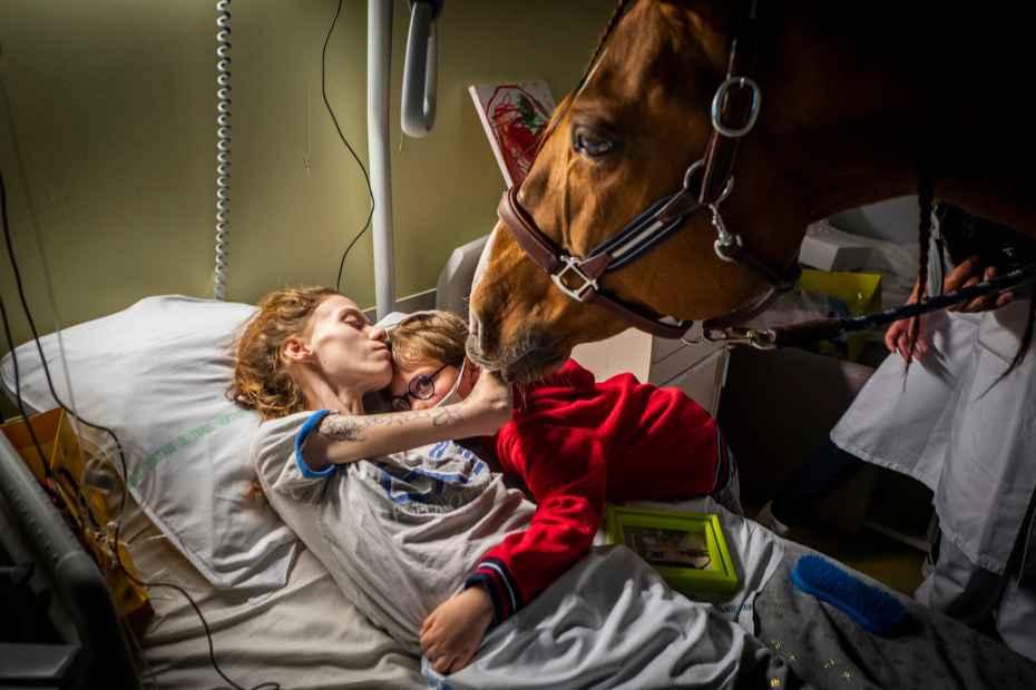 """France-Calais 30/11/2020 Centre de soins palliatifs de l'hôpital de Calais.Manon, 24 ans, atteinte d'un cancer généralisé enlacés son fils Ethan 7ans en présence de Peyo qui se laisse toucher et caresser par elle seule.""""Avec Peyo, on essaie de recréer de la vie dans la fin de vie, pour se battre, créer une énergie aux cotés des familles et des soignants."""" me dit Hassen"""