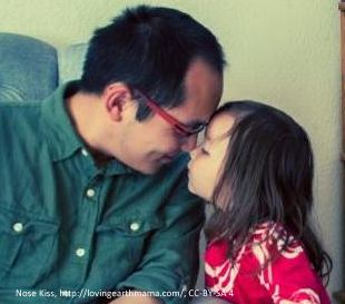 Dad and daughter touch noses.