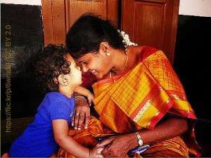 Mother in sari and boy touch noses.