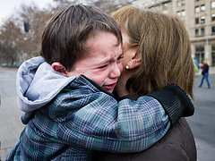 crying boy clutches to mother who holds him close- maybe they have to separate