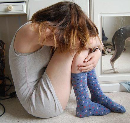 Upset teen girl sits, head hidden, blocking us out.