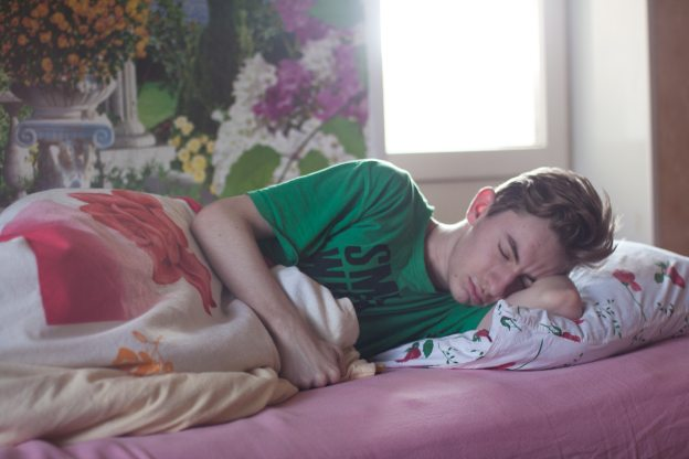 Young man sleeping, pink sheet green shirt.