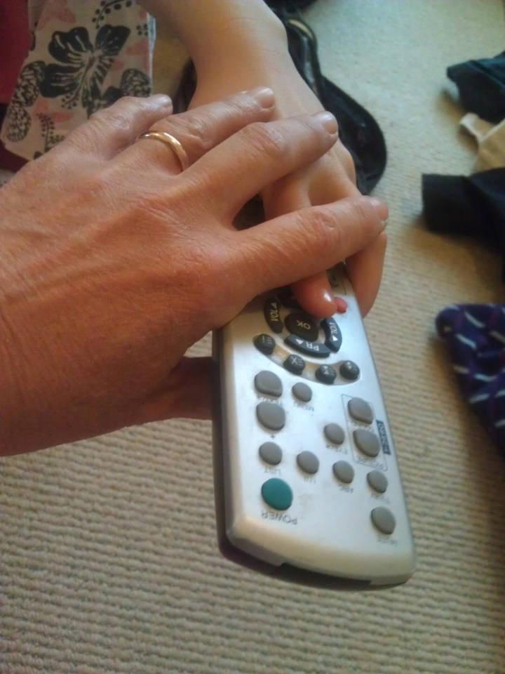 Mother puts out hand on television remote control to limit television time
