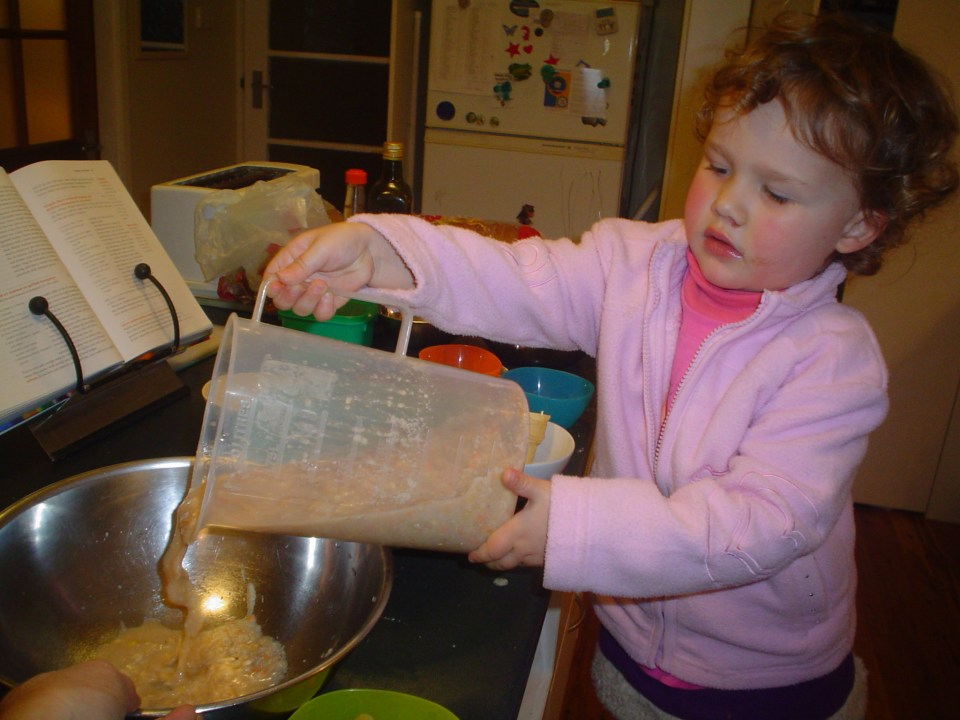 Young child - 2.5 years old, concentrates as she pours from a jub into a mixing bowl.
