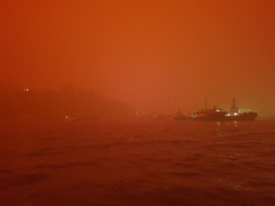 Orange smoke haze across water, from bushfires
