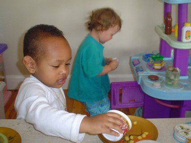 Two 2 year olds busy playing at cooking