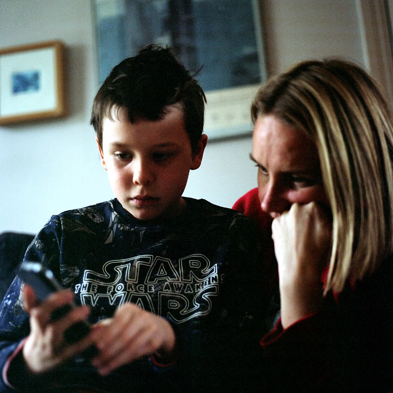 Boy shows his mother something interesting on his mobile phone