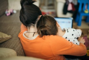 Mother and daughter snuggle together looking at a screen.