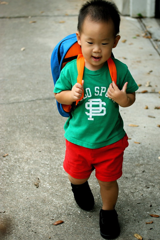 Young asian boy walks to school with backpack