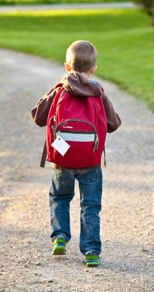 Young boy walks along path with big red backpack