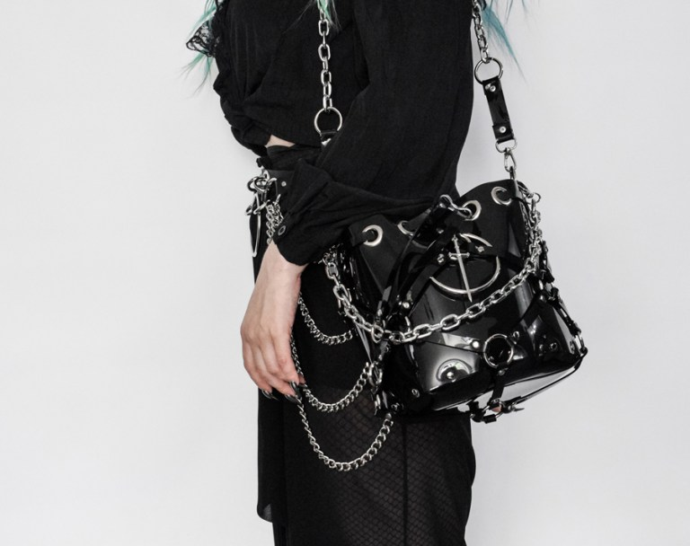 goth girl carrying the pvc vinyl bag with chains and sword symbol