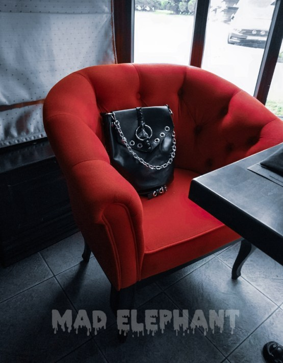 black leather bag on the red armchair