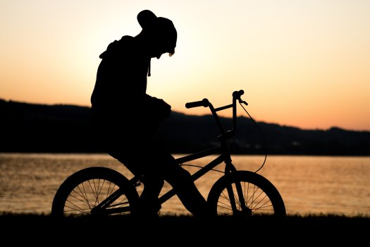 shadow of boy on bicycle against a sunset