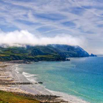 La Baie d'Écalgrain, cielo azzurro ricoperto di nuvole, mare turchese e scogliere