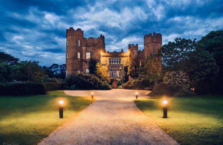 Castelli d'Irlanda: Malahide Castle visto dal viale principale illuminato. Incorniciato dalla vegetazione e sovrastato dalle nuvole tipiche dei cieli d'Irlanda