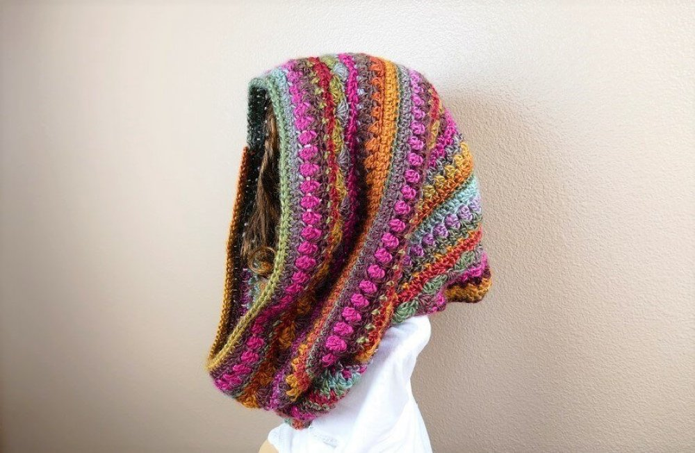 This hooded cowl crochet pattern creates a lovely self-striped, multicolored cowl that can be worn as a head wrap for those snowy winter days. It