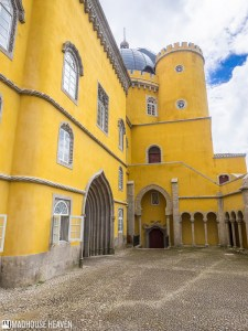 stone courtyard surrounded by yellow castle walls with islamic architectural influences