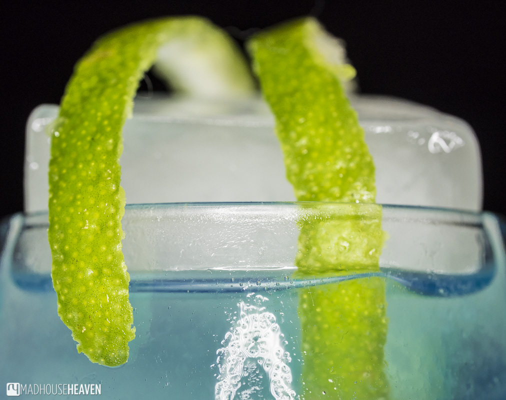Close up, lime peel twist, large ice cube, Iceberg cocktail with blue curacao