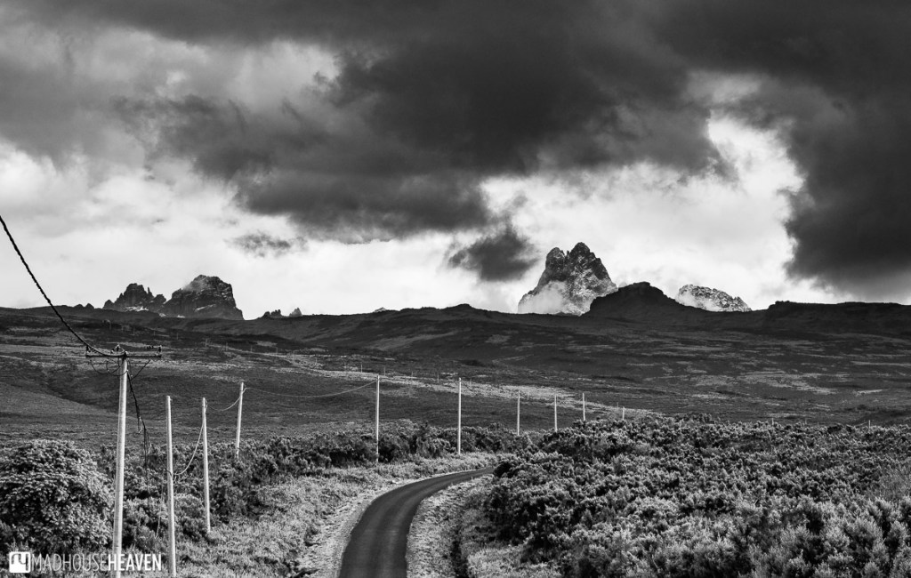 Black and white photograph of the Mount Kenya peaks, covered by the ever changing clouds, just a few steps behind the Sirimon Gate