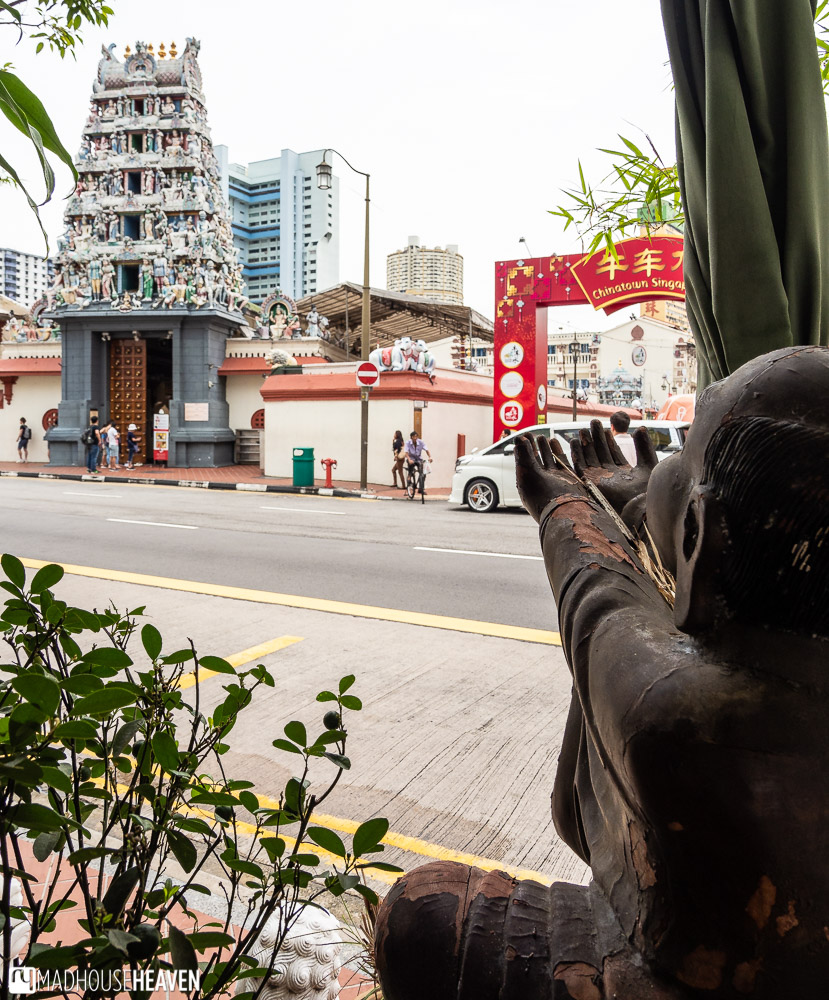A buddha with outstretched arms framing Singapore's Chinatown