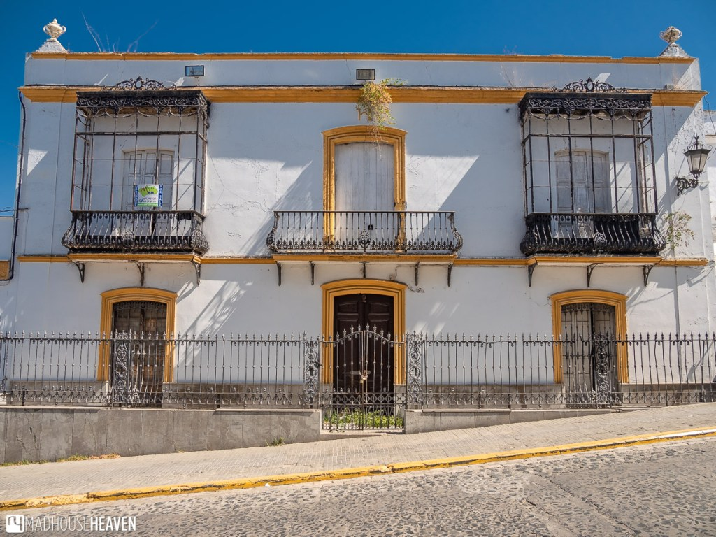 An old white painted house in Arcos de la Frontera with yellow details, set against a stark blue sky