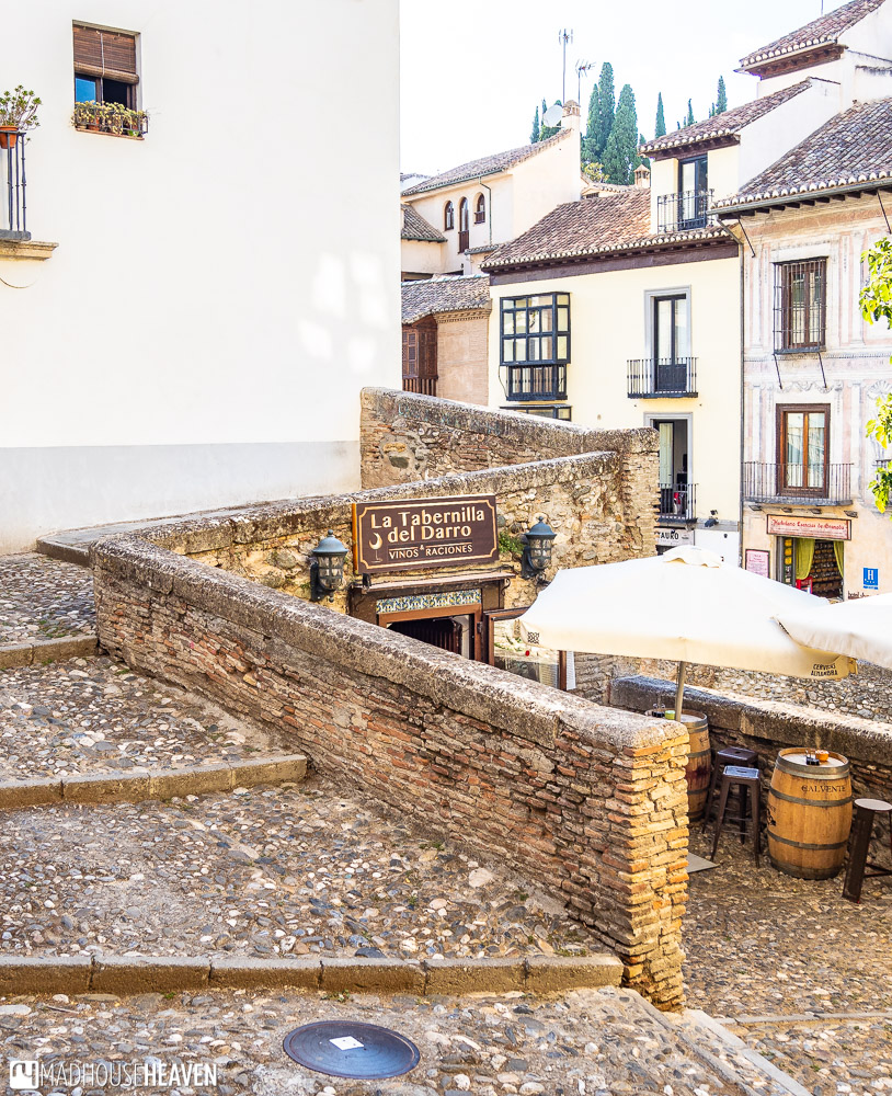 Cobble stoned Spanish staircase that goes over an entrance into a cellar like restaurant