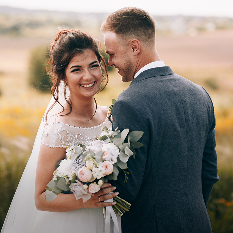 A newlywed couple smiling at the camera