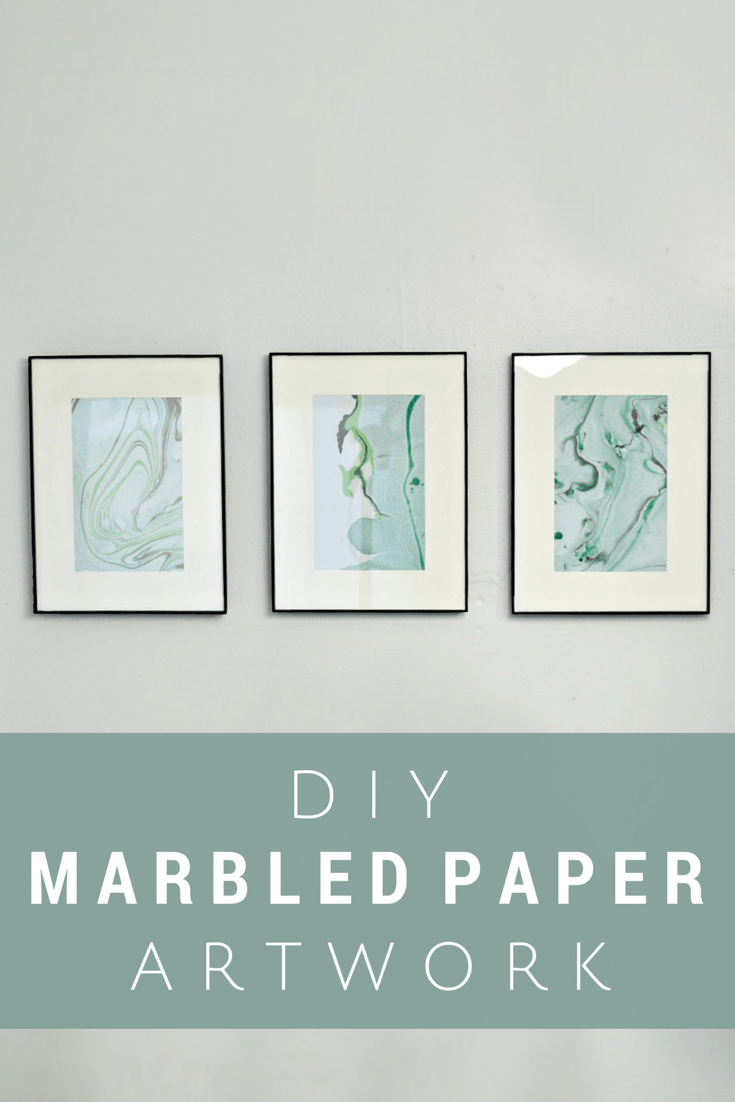 three framed marbled papers on a blue wall