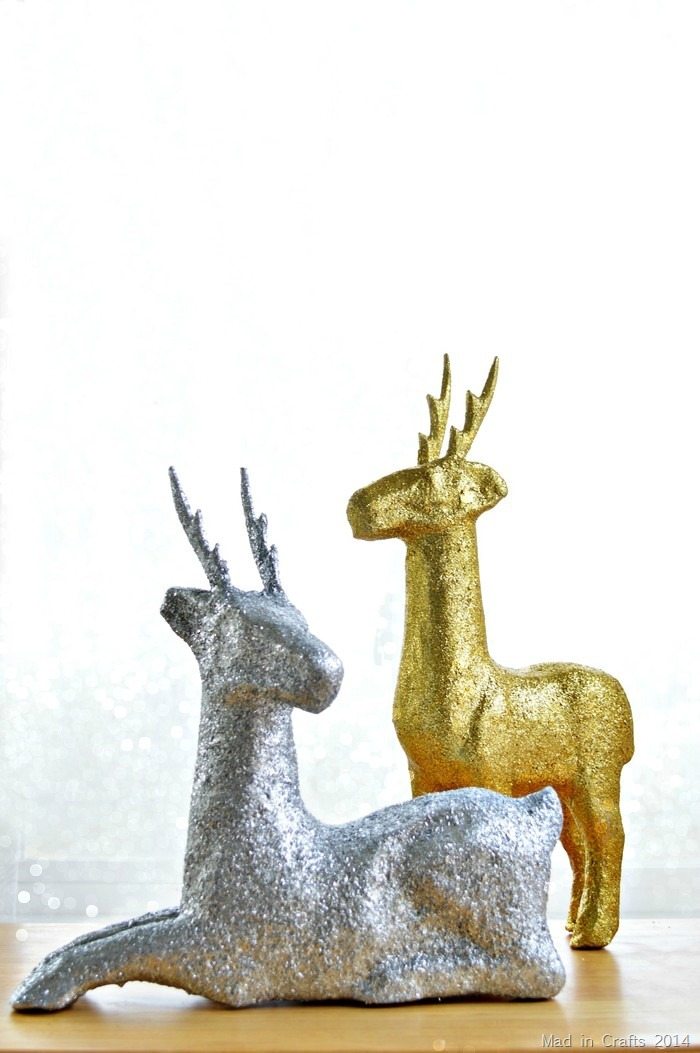 DIY glittery paper mache deer in front of a bokeh background