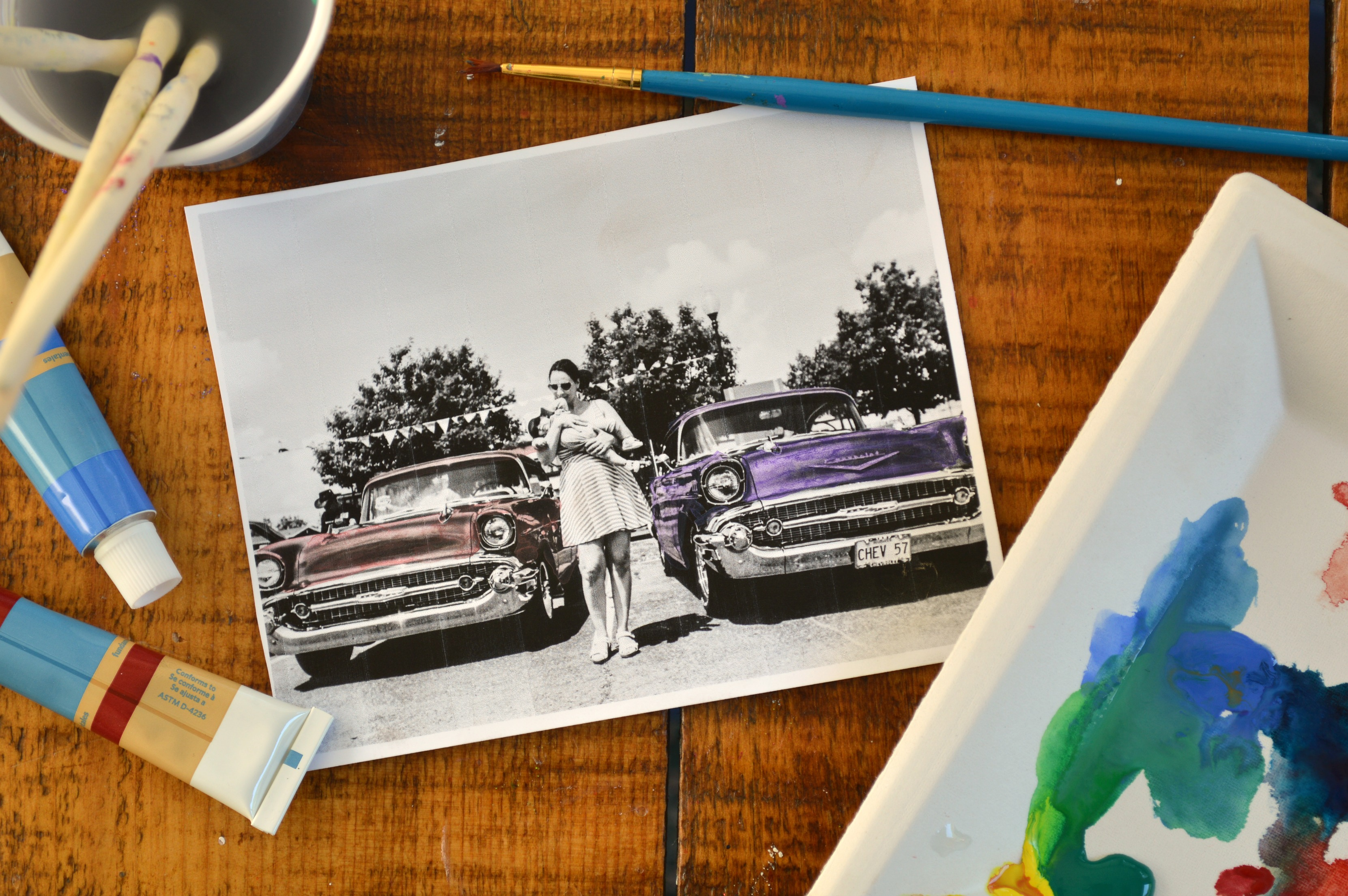 painted black and white photograph of a woman and vintage cars
