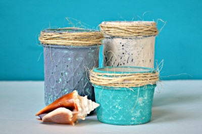 blue and white beachy painted mason jars on a blue background with a seashell