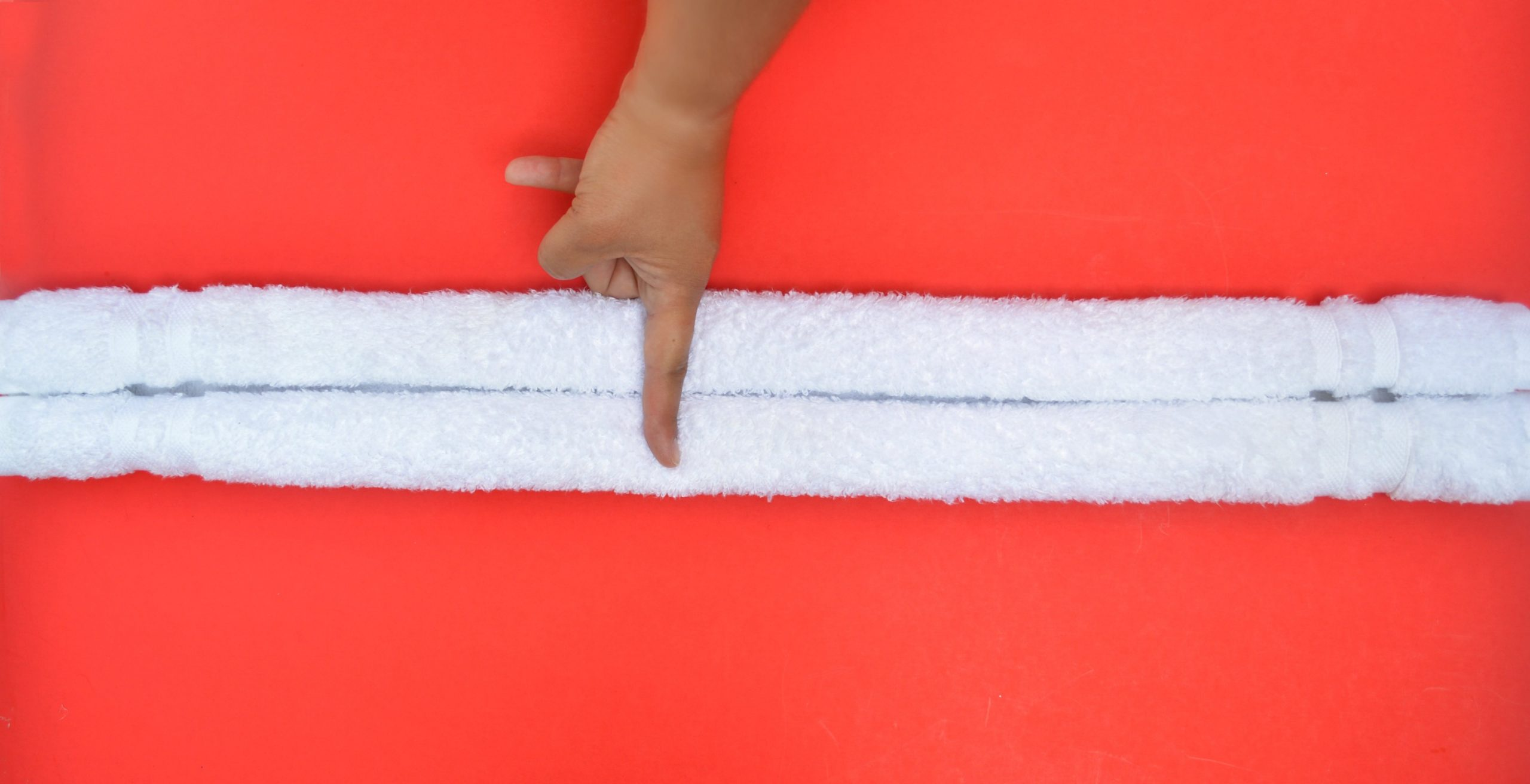 finger on the middle of a rolled towel on a red background