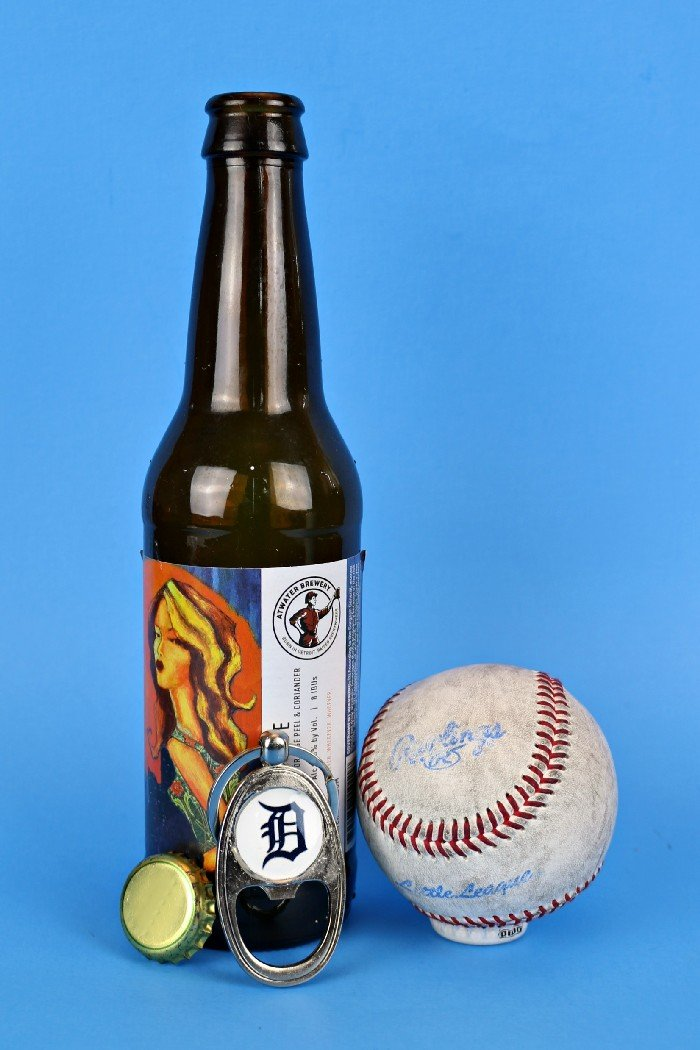 Detroit Tigers bottle opener key chain next to a bottle of beer and a baseball